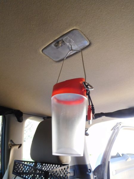 I stuck a 3M Command hook (the adhesive hooks that you can remove by pulling a tab) into the light in the middle of the back of the SUV, and I hang the lantern from the hook.