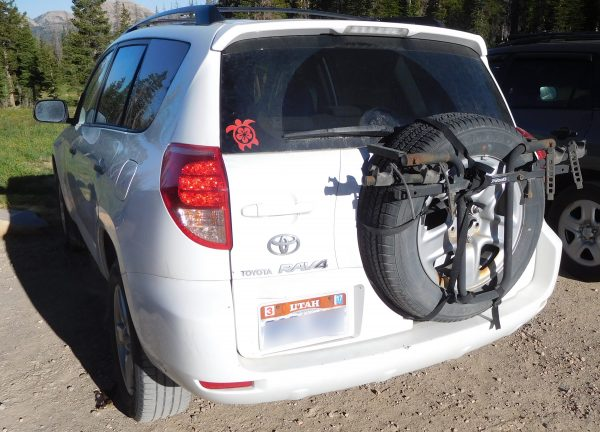 A RAV4 with a bike rack attached to the spare tire.