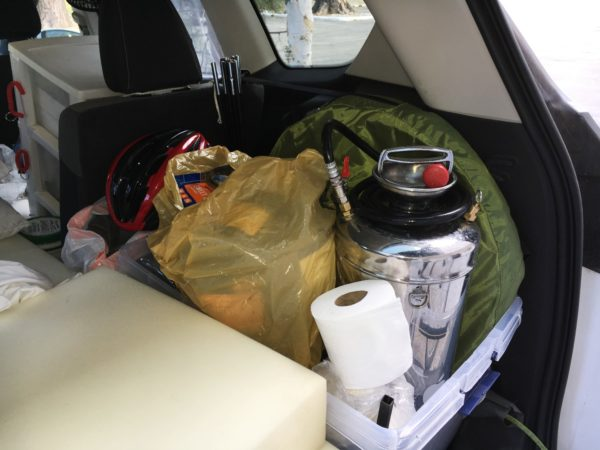 The bin next to the bed in the rear cargo area.