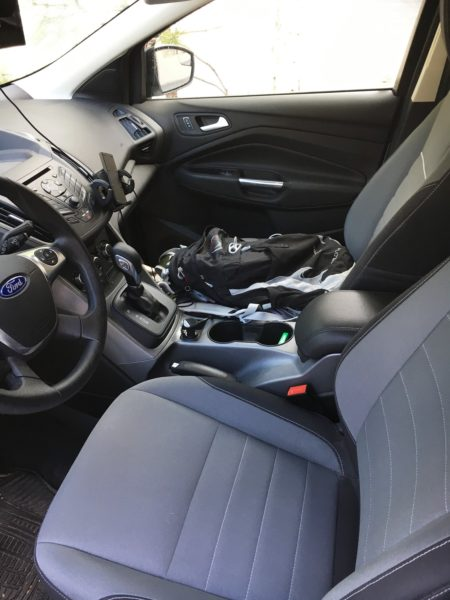 A side look at the two front seats. He's using the front seat and the floor in front of the seat for storage. Note also the vent-mounted phone holder and signal booster.