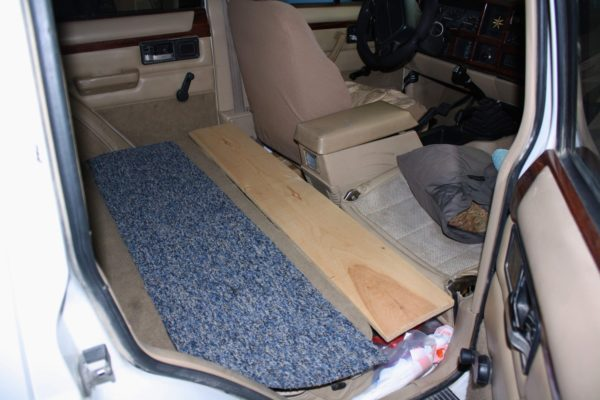 Bridging the gap: the space between the front and rear seats is covered with a simple plank and strip of carpet (a scavenged scrap from a local flooring outlet).