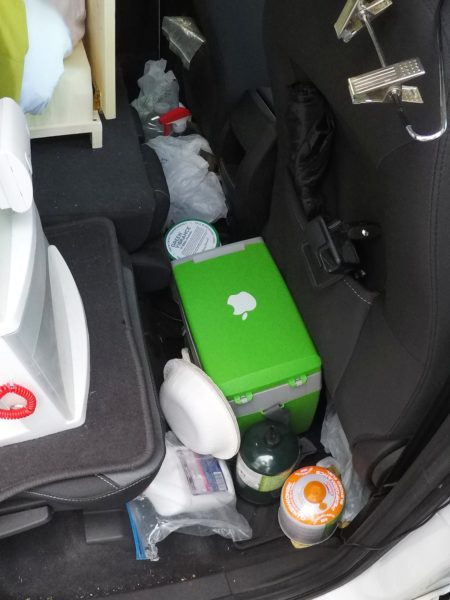 The cooler, stove fuel, and shoes stored on the floor behind the front passenger seat.
