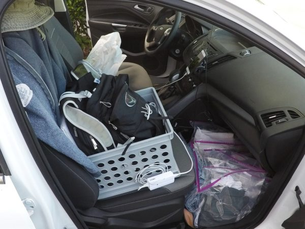 A plastic bin on the front passenger seat helps Ted organize his backpacks.