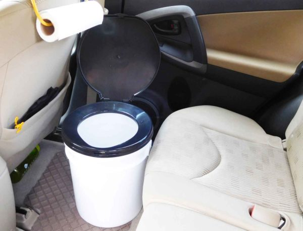 A bucket toilet inside of an SUV